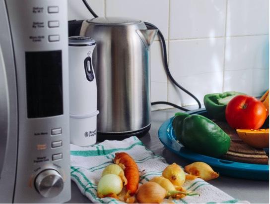 Three kitchen appliances sitting next to vegetables on a kitchen towel