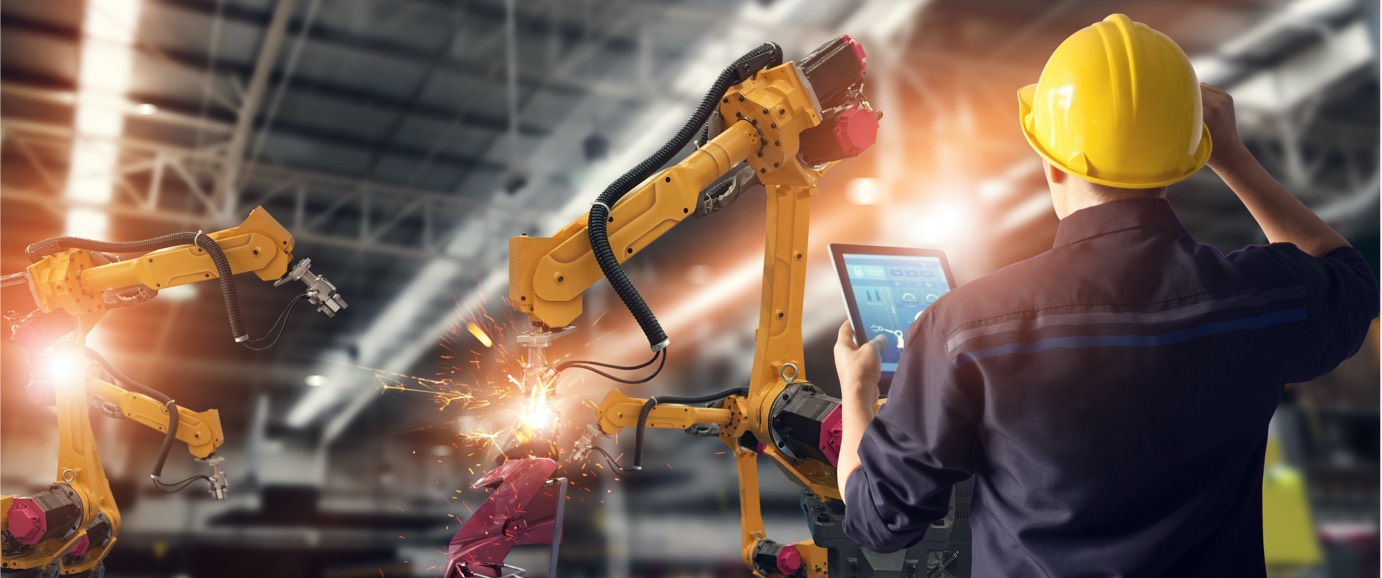 A view from behind of someone wearing a hardhat and holding a digital tablet standing in front of a piece of machinery