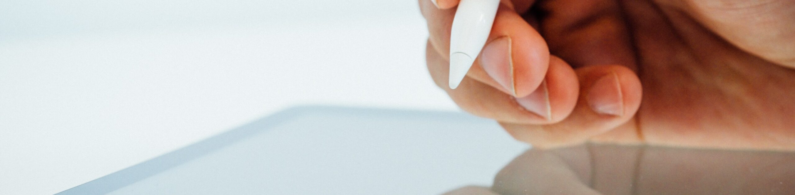 Close up of hand using a smart pen on a tablet.