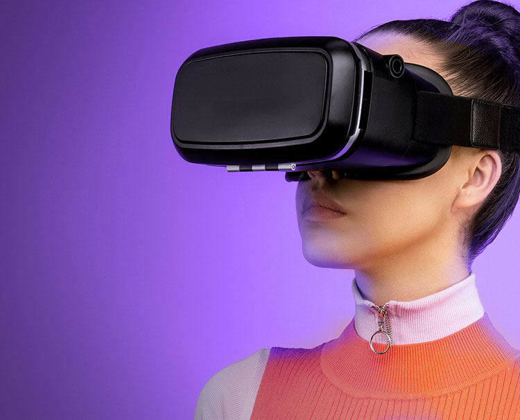 Image of a woman wearing virtual reality goggles and orange dress with a purple background