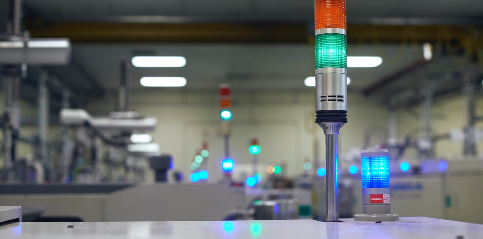 Close up image of a colored indicator light with factory in the background